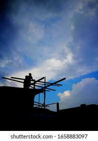 silhouetted man working on tower in sky