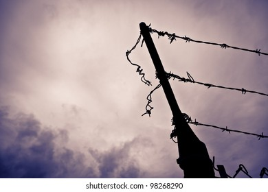 A silhouetted metal fence post with barbed wire that has been cut and left hanging against a dramatic purple hued stormy sky.