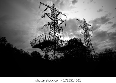 A silhouetted pair of electricity pylon towers behind a tree line with a moody looking sky and clouds
