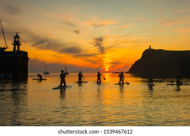 Silhouetted people paddle boarding in Port Erin Bay in the Isle of Man