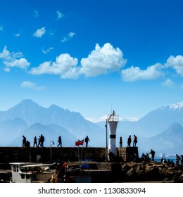 Silhouetted people relaxing in Antalya harbor over blue sky and high mountains