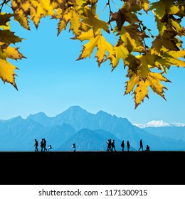 Silhouetted  people relaxing on street over blue sky and high mountains