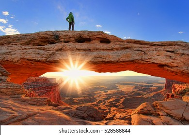 Silhouetted person standing on top of Mesa Arch, Canyonlands National Park, Utah