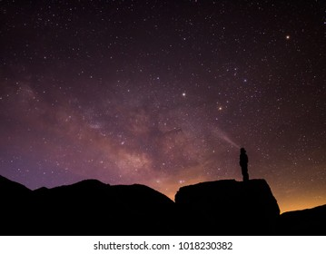 Silhouetted person stands atop boulder with light beam looking up at the milky way , stars, and sunrise.