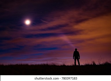 Silhouetted person stands atop a grassy hill with a light beam looking up at the milky way, moon, and colored clouds at sunrise.