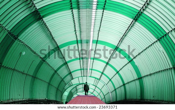 Silhouetted Person walking on red pathway at green metro tube tunnel