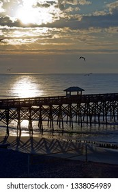 Silhouetted pier with soccer net in the foreground on Folly Beach, South Carolina at sunrise as sea birds wheel around the sky