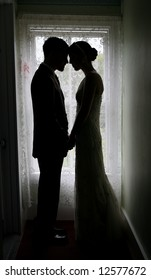 Silhouetted portrait of a bride and groom standing in front of a lacy window.