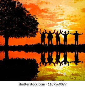 Silhouetted and reflection in still water sunset background.They are standing with tree and show hand together.They are enjoying and  watching the evening glow together.Photo concept for Silhouetted.
