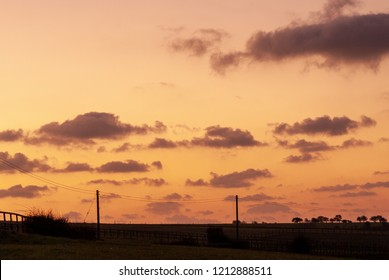 Silhouetted ridgeline with telegraph poles and clouds