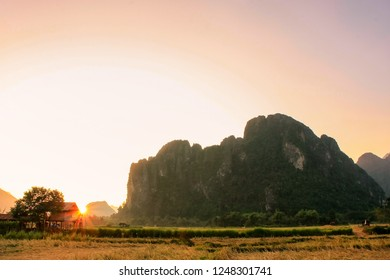 Silhouetted rock formations at sunset in Vang Vieng, Laos. Vang Vieng is a popular destination for adventure tourism in a limestone karst landscape.