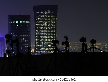 Silhouetted row of cameras on tripods lined up overlooking an illuminated city with skyscrapers on a rooftop at night
