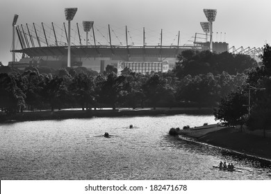 Silhouetted rowers on the Yarra River with the Melbourne Cricket Ground in the background.