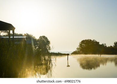 Silhouetted shacks during a beautiful, misty golden sunrise on Lake Panasoffkee in Florida.