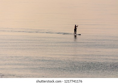 Silhouetted stand-up paddle boarder on a flat calm sea