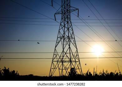 A silhouetted steel power tower at sunset.
