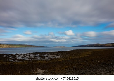Silhouetted stone beach with deep blue sea and sky, clouds rising over mountains beyond.