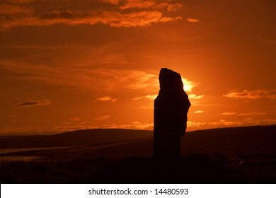 A silhouetted stone of the Ring of Brodgar during sunset
