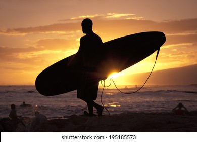 Silhouetted surfer at Waikiki Beach approaches the water at sunset.