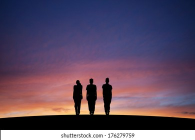 silhouetted three teenagers standing straight in sunset