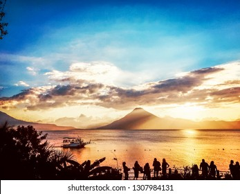 Silhouetted tourists watch sunset over Lake Atitlan & San Pedro volcano as ferry boat cruises past, Guatemala, Central America
