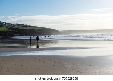 Silhouetted unidentifiable people walking on Polzeath beach in North Cornwall with intentional sun flare reflecting from the wet sand and surf