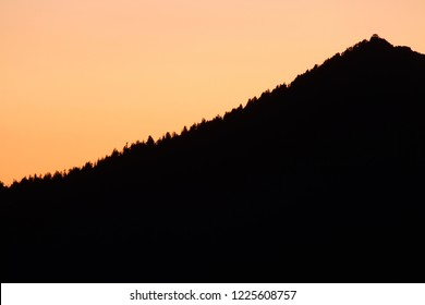 Silhouetted Watchman Peak and Watchman fire lookout at sunset, from Cloudcap Overlook, Crater Lake National Park, Oregon, USA