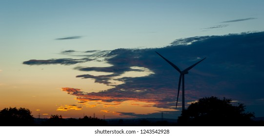 A silhouetted wind turbine against a dark sky at sunset