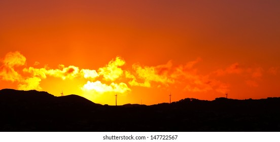 Silhouetted of Wind turbine standing on the top of mountain with dramatic sunset