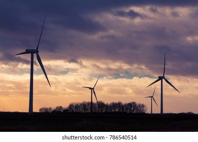 Silhouetted wind turbines at sunset in a rural English landscape