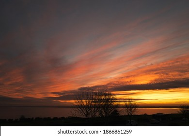 Silhouetted winter trees with a beautiful cloudy sunset over Pegwell Bay in Ramsgate, kent.