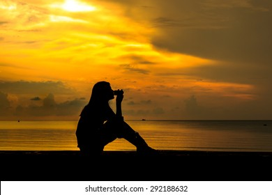 Silhouetted of woman drinking coffee near beach at sunset.