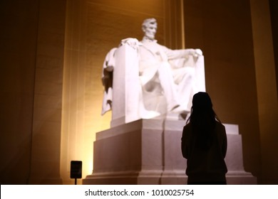 A silhouetted woman gazes at the statue of Abraham Lincoln at the Lincoln Memorial, Washington, D.C.