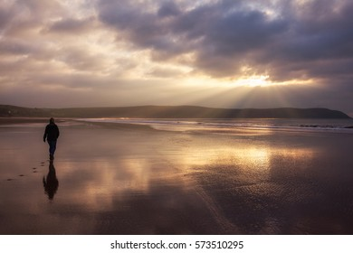 Silhouetted woman walking alone on the beach at Woolacombe Sands in North Devon, England, UK