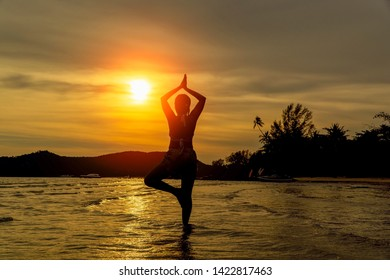 silhouetted young girl relax yoga at sea with twilight sunset