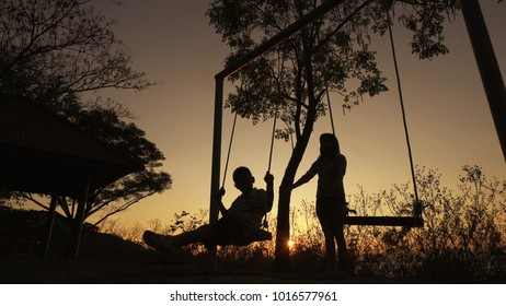 Silhouetted young mother with boy enjoying beautiful sunny day, swinging on swing set. Red orange sunset background.