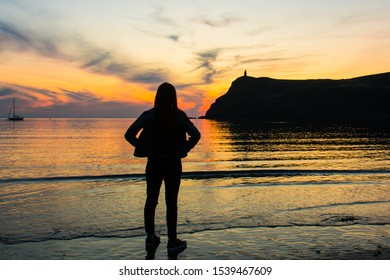 Silhouetted young woman looking at the sunset at Port Erin in the Isle of Man