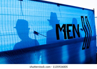Silhouettes of 4 men using the toilets at a music festival.