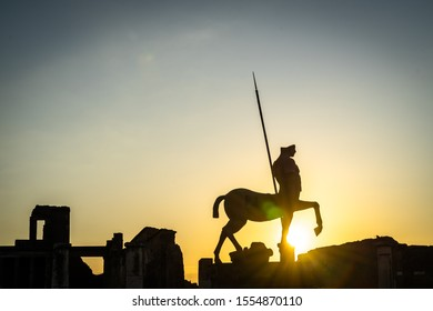 Silhouettes against the sky at sunset in Pompeii ancient city. Centaur statue by Igor Mitoraj and ruins of columns.