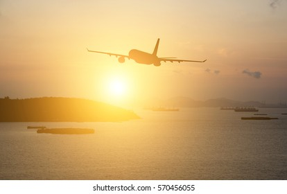 Silhouettes airplane on sunset in the city background