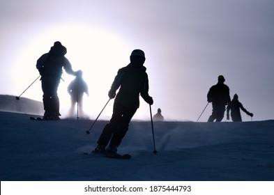 Silhouetten von Alpin-Skifahrern, die in kontrastlichter Helligkeit die Skipiste hinunter fahren