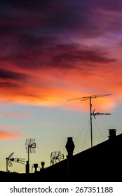 Silhouettes of antennas and chimneys backlit at sunset with colorful sky clouds