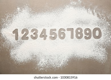 Silhouettes of Arabic numerals on scattered flour