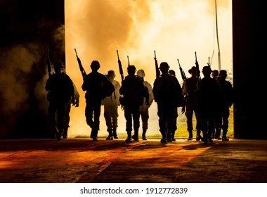 Silhouettes of army soldiers in the fog against a sunset, marines team in action, surrounded fire and smoke, shooting with assault rifle and machine gun, attacking enemy