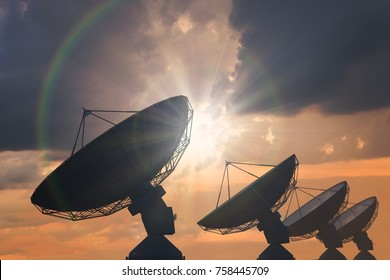 Silhouettes of array of satellite dishes or radio antennas at sunset.