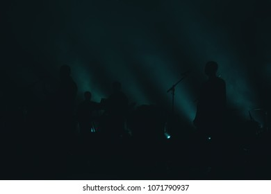 silhouettes of artists on stage