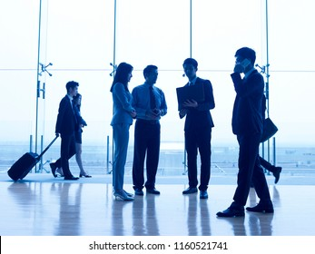 silhouettes of asian corporate executives discussing business in airport terminal building.