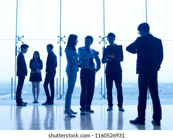 silhouettes of asian people standing discussing business in modern office.