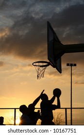 silhouettes of basketball players at the sunset
