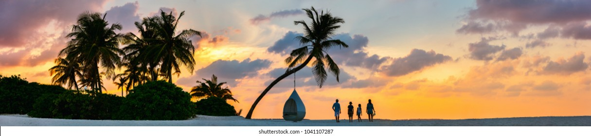Silhouettes of beautiful family of four with kids at tropical beach during sunset, panoramic photo perfect for banner